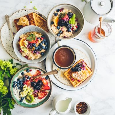 Nice breakfast or brunch setting with waffles, pancakes, fruit, honey and more.
